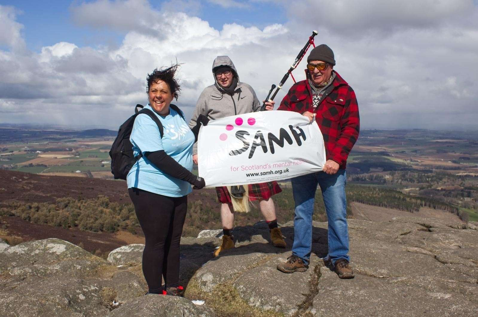 Emma Strathdee at the top of Bennachie during her last climb with bagpiper Calum Lawrie and her dad Gordon Pratt.