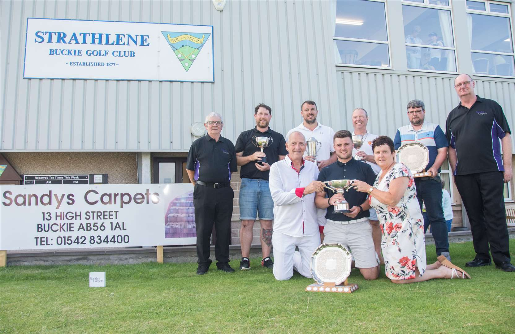 Scratch winner Craig Bain (front) is presented with his trophy by Sandy and Meg Sievwright from sandy's Carpets. (Back from left) Sandy Mackie (club captain), Darryl McGregor (Badenoch Cup), Richard Simpson (Banffshire Advertiser Cup), Alan Ross (Gordon Cup), Mark Auld (Craigendarroch Cup and Sammy Coull (match and handicap secretary).Picture: Becky Saunderson. Image No.044547